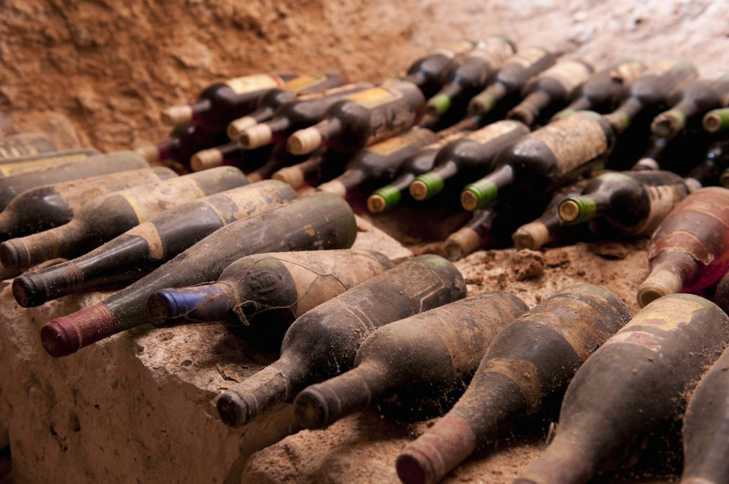 Old wine bottles on a stone step, a cave